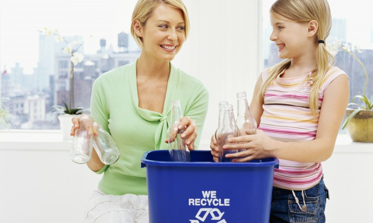 mother and her daughter putting bottles in a garbage bin