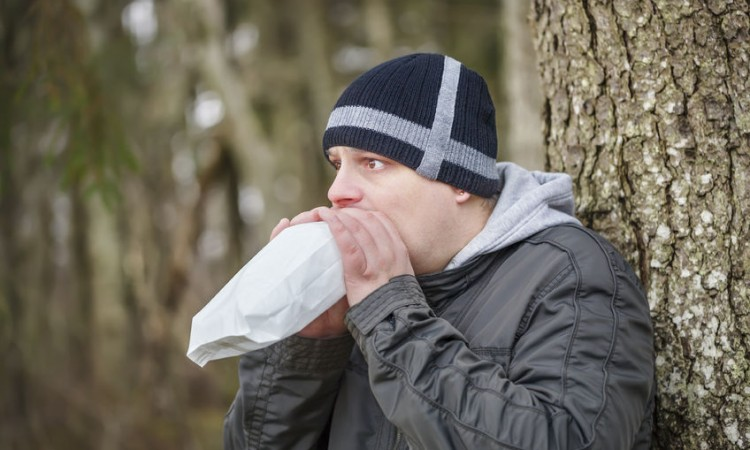 26514081 - worried man breathe into a paper bag near tree