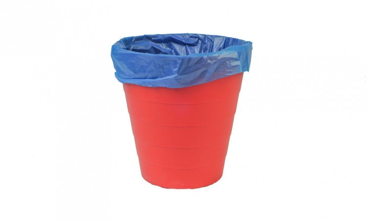 Red plastic trash or garbage bin on white background. Selective focus